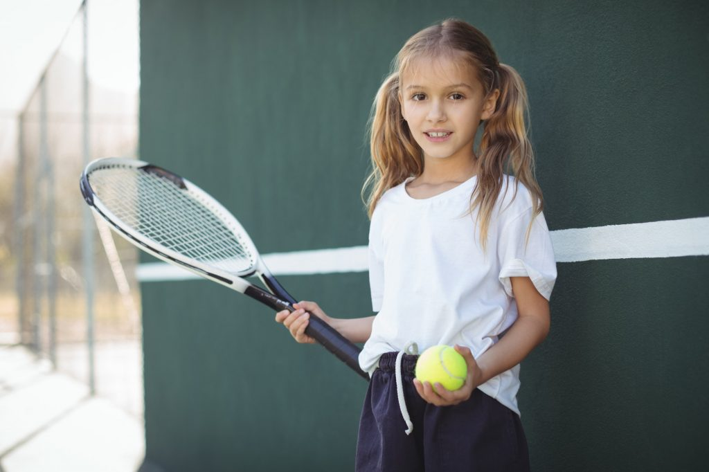 Girl holding tennis racket and ball
