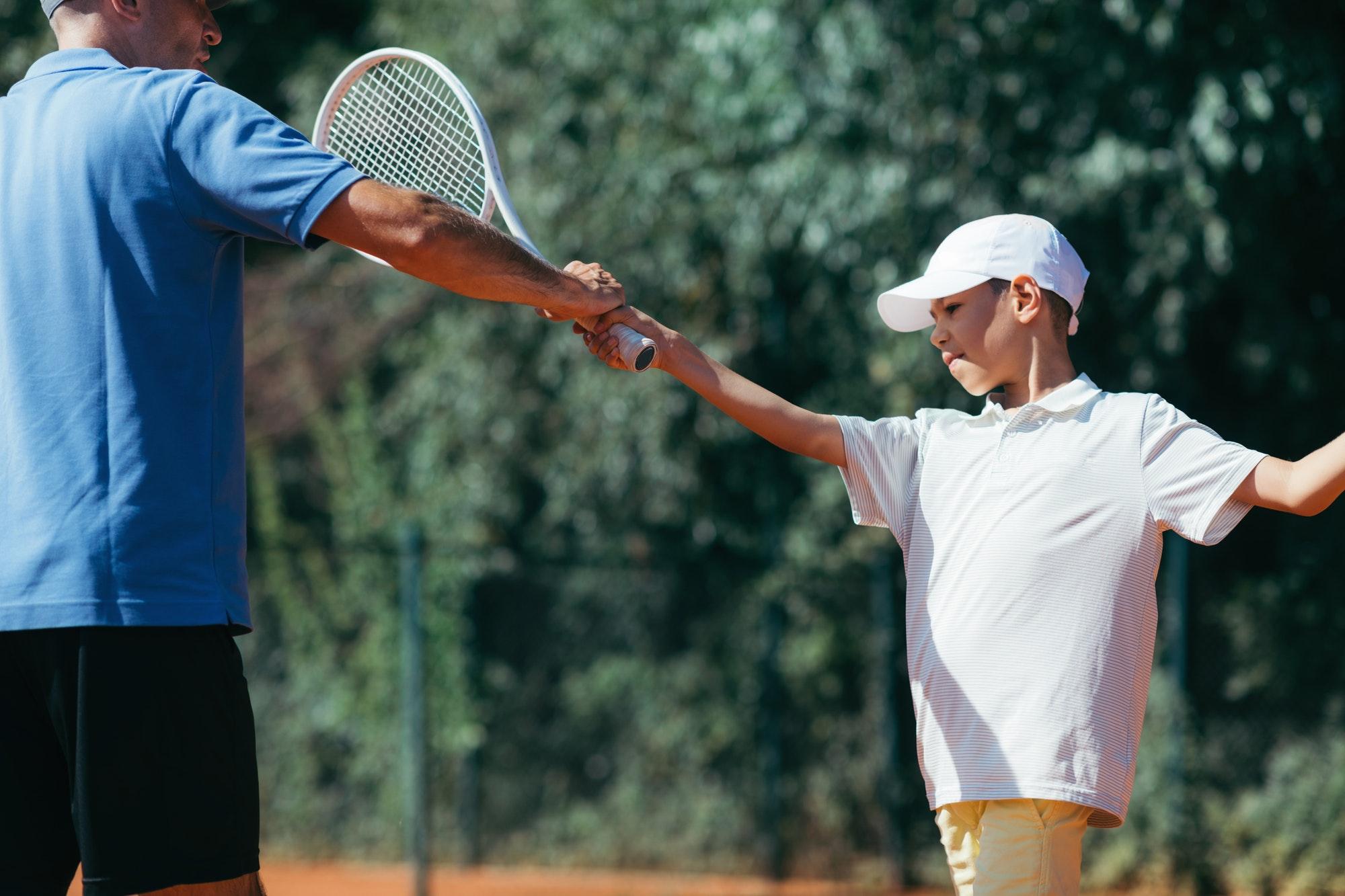 Tennis Lesson. Smiling Coach Explaining Tennis Technique to a Boy