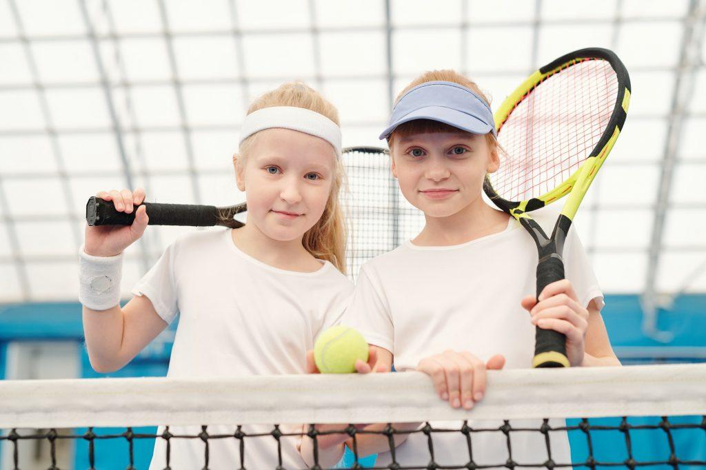 Two cute friendly girls in white sportswear holding tennis rackets on shoulders